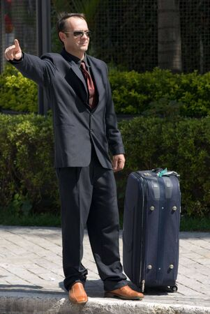 flagging: Latin american businessman in a suit waiting on the curb with his luggage with his arm out to flag someone down Stock Photo