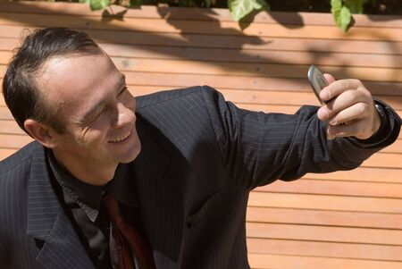 A businessman in a black pinstripe suit checking his cellphones caller id. Stock fotó