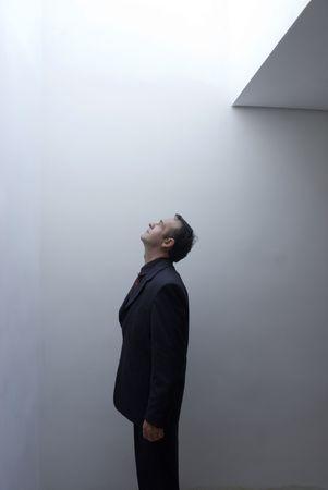 Latin american businessman standing under a skylight gazing skyward