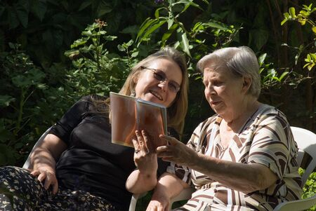 Latin american woman and her elderly mother reading together in a lush green garden Stock Photo - 2904326