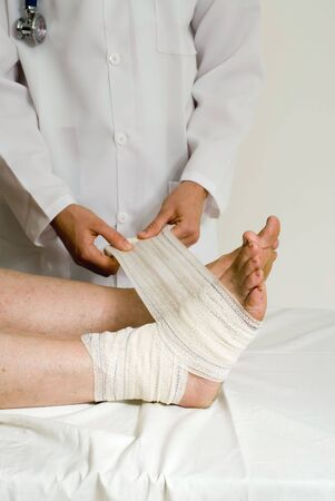 Doctor wrapping a patients ankle with a bandage. Isolated.