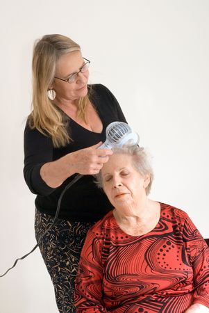 Woman drying her elderly mothers hair. Isolated against a studio background photo