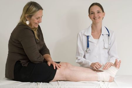 Young female doctor wrapping an older female patient's ankle with a bandage Stock Photo - 2904320