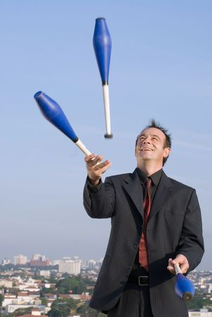 skillfully: A smiling businessman skillfully juggling outdoors in a suit.