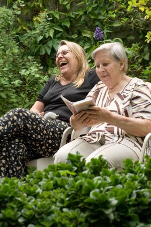 Latin american woman and her elderly mother laughing heartily while reading together in a lush green garden