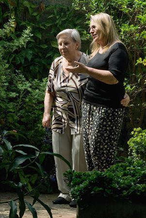 A shot of an adult child with her mother, walking in garden. Stock Photo - 2904329