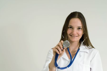 Young female doctor holding up her stethoscope and smiling. Isolated. Stock Photo - 2917237