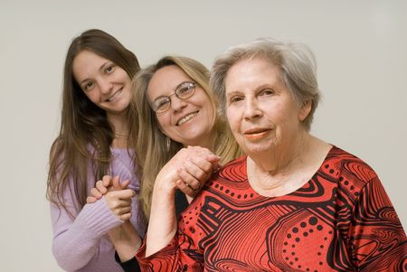 Daughter, mother and grandmother with their hands clasped smiling at the camera. Isolated. Stock Photo