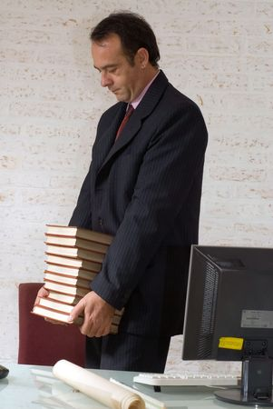 Business man carrying a big stack of books photo