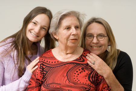 Daughter and mother on either side of their grandmother. Isolated. photo