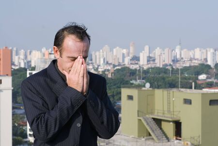seemingly: Latin american business man standing on a city rooftop with his eyes closed and his hands over his face seemingly lost in thought Stock Photo