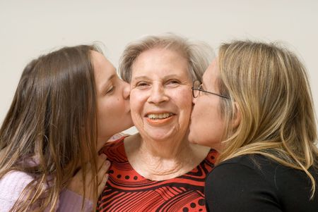 Mother and daughter on either side of their grandmother planting a kiss on her cheek. Isolated photo