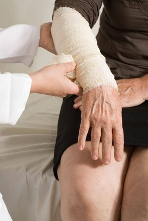 Younger female doctor wrapping a bandage around the forearm of an older female patient. Isolated.