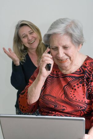 Woman standing behind her elderly mother as the older lady uses a laptop and talks on a cell phone photo
