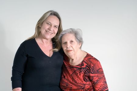 Woman and her elderly mother side by side. Isolated. photo