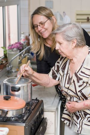 Woman and her elderly mother cooking a meal together
