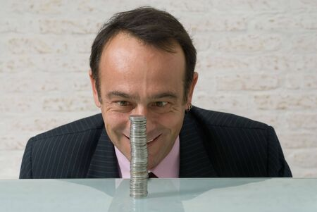 maniacal: A shot of a businessman, with maniacal expression on his face, looking at a stack of quarters.