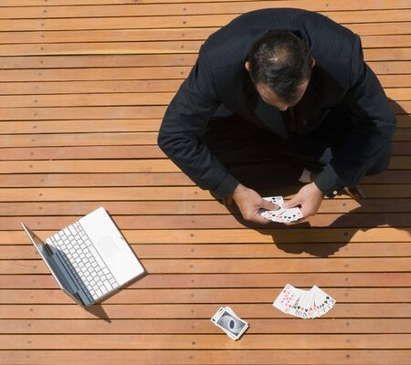 goofing: Latin american business man sitting cross legged with playing cards and his laptop computer in front of him