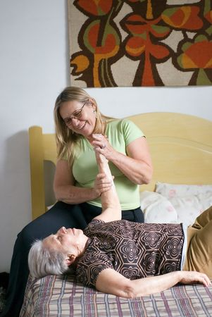homecare: Woman helping her elderly mother with stretching and physical therapy exercises