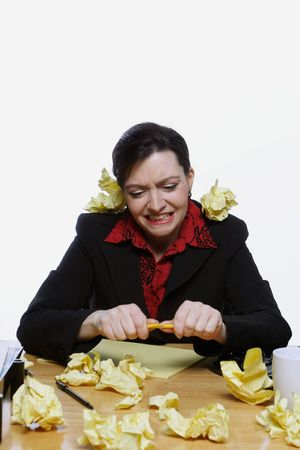Woman in a business suit balancing a pencil under her nose surrounded by crumpled up pieces of yellow paper. Isolated against a white background Stock Photo - 2987052