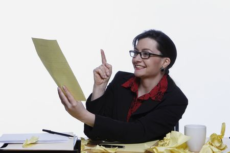 Businesswoman holding up a sheet of yellow legal paper and pointing at it with a smile on her face Stock Photo - 2986954