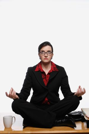Woman in a business suit sitting cross-legged in a yoga pose on top of her desk at work. Isolated against a white background Stock Photo - 2986822