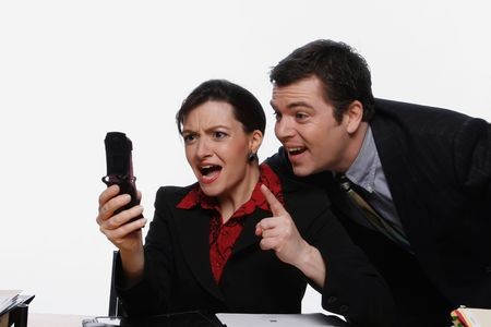 Businesswoman and businessman staring at her cell phone and smiling Stock Photo - 2986999