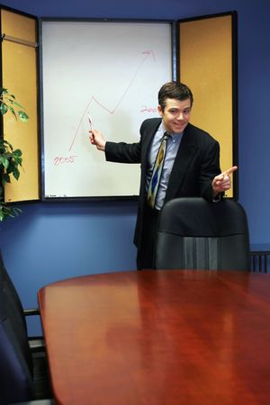 Man in a business suit standing at a whiteboard and presenting information photo