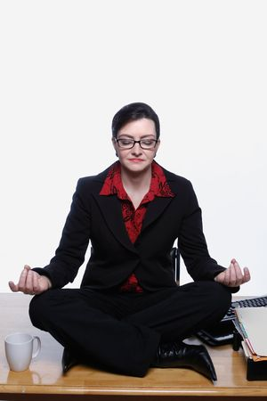 Woman in a business suit sitting cross-legged in a yoga pose on top of her desk at work. Isolated against a white background Stock Photo - 2986978