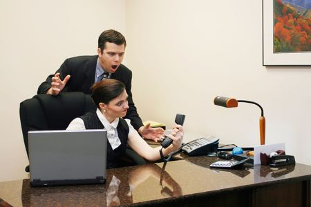 Male and female business colleagues arguing over who should take a phone call Stock Photo - 2987185