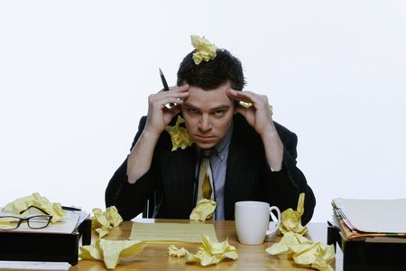 Businessman sitting at his desk surrounded by and covered in balls of yellow notepaper. He has his hands on his head. Isolated against a white background. Stock Photo - 2987055