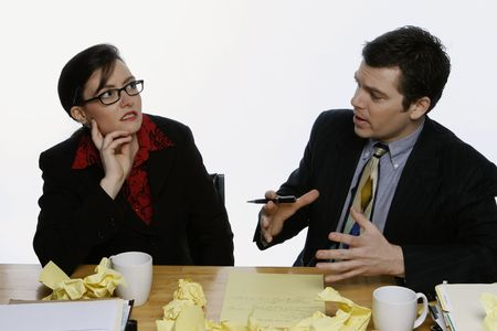 A shot of a business woman and man sitting at desk.  The man is trying to explain something to the woman, who has a preplaxed look on her face.
