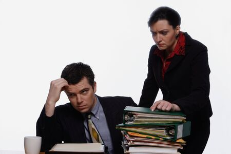 causcasian: Businessman looking dejected as his female boss hands him more work. Isolated against a white background