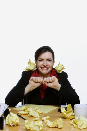 Woman in a business suit balancing a pencil under her nose surrounded by crumpled up pieces of yellow paper. Isolated against a white background