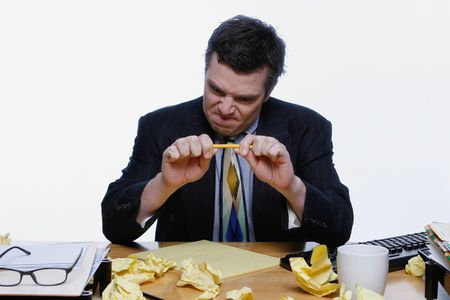 breaking up: Man in a business suit sitting at his desk frustrated and trying to snap a pencil. Surrounded by crumpled up pieces of paper. Isolated against a white background.