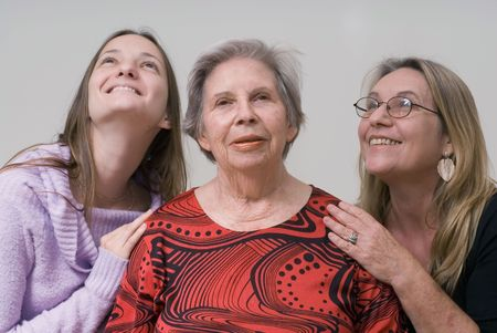 A shot of three generations of women (daughter, mother, grandmother) with the eldest in the center. Stock Photo - 2987451