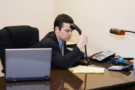 handset: Man in a business suit sitting at his desk hitting himself with his handset