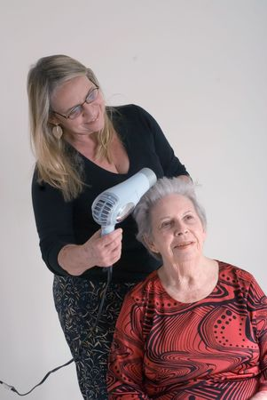 A shot of an adult child doing her elderly mothers hair. Фото со стока