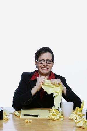 Businesswoman surrounded by crumpled up pieces of notepaper holding up a sheet and throwing a piece at the camera in disgust Stock Photo - 2986956