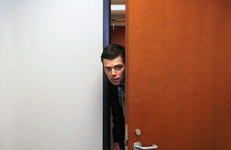 Businessman poking his head furtively through a doorway