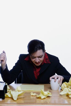 stabbing: Woman in a business suit stabbing her pen in the air with frustration, surrounded by balls of crumpled yellow notepaper. Isolated against a white background. Stock Photo