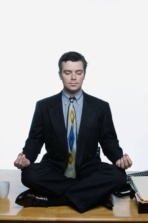 Man in a business suit sitting cross-legged in a yoga pose on top of his desk at work. Isolated against a white background