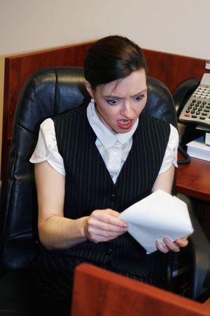 creditors: Businesswoman opening an envelope and grimacing at whats inside Stock Photo