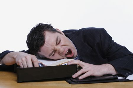 slacker: Businessman yawning at his desk. Isolated against a white background.