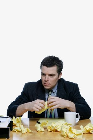 glum: Businessman sitting at his desk looking dejected surrounded by scraps of yellow notepaper