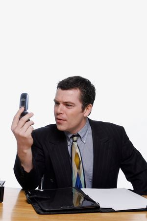 quizzical: Businessman looking at his cellphone screen with a quizzical expression on his face. Isolated against a white background.