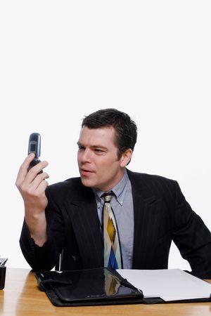 quizzical: Empresario busca en su m�vil con pantalla quizzical una expresi�n en su rostro. Aislados sobre un fondo blanco.
