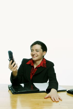 Businesswoman looking at her cell phone screen and smiling. Isolated against a white background. photo