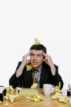 Businessman sitting at his desk surrounded by and covered in balls of yellow notepaper. He has his hands on his head. Isolated against a white background. Stock Photo - 3002618