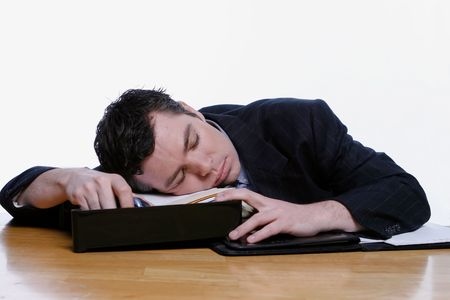 slacker: Businessman fast asleep at his desk. Isolated against a white background.